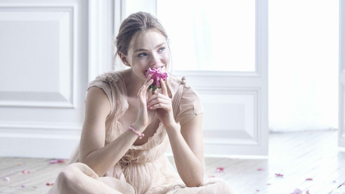 Flora Chic Behind the Scenes image - woman sitting on the floor smelling a flower