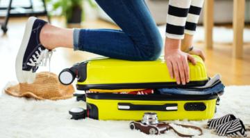 Tipps Packen fürs Handgepäck Frau mit vollem Koffer Reisen123RF