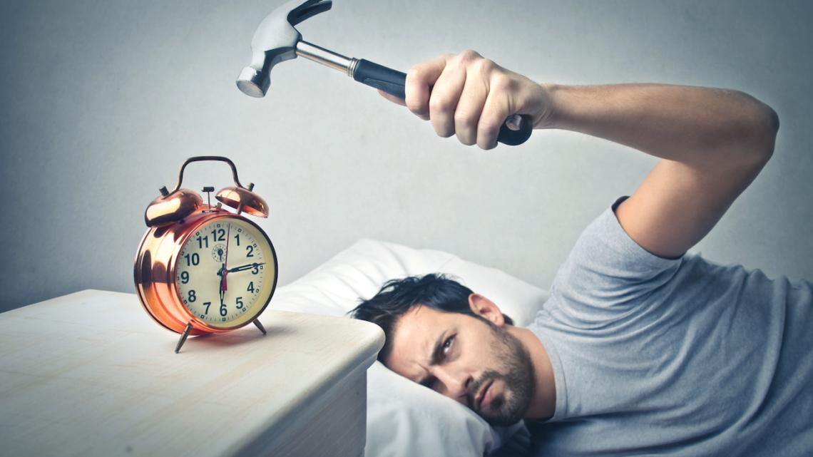 Schlafen Tipps Mann mit Wecker und Hammer