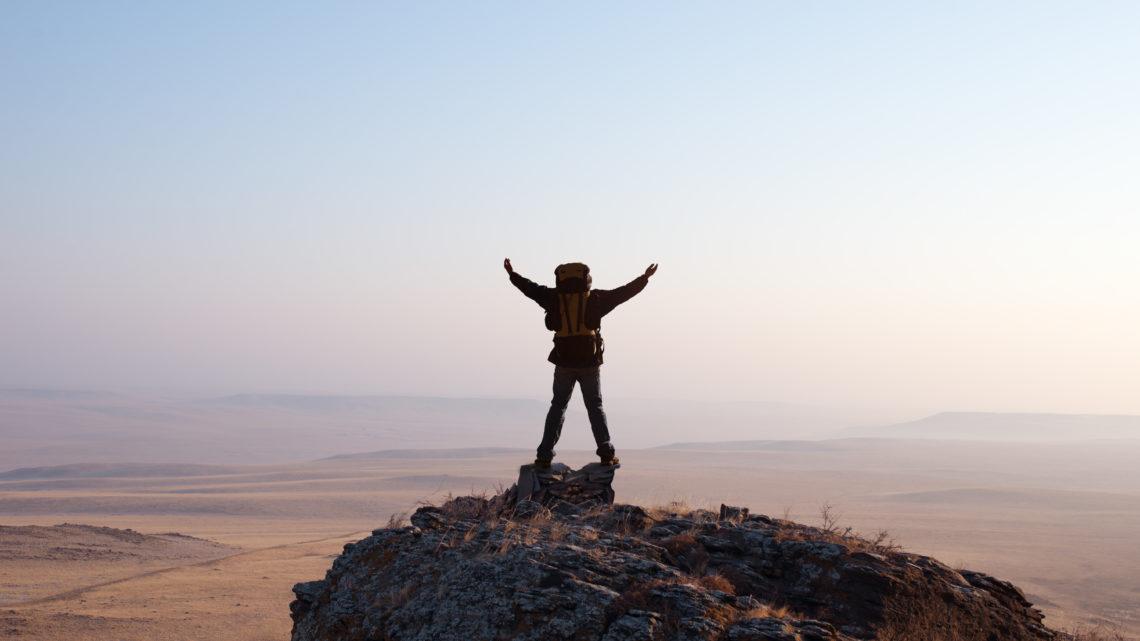 Alleinreisende Ideen Destinationen Wanderer auf Bergspitze 123RF worldofwellness